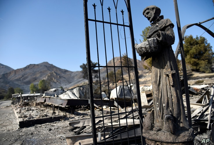 A religious statue stands amongst destroyed properties in the Seminole Springs Mobile Home Park, Nov. 11, 2018, after wildfires tore through the neighborhood in Agoura Hills, California.