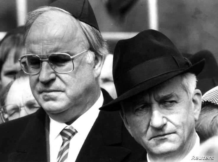 Helmut Kohl stands with former West German President Richard von Weizsaecker (R) in this April 21, 1985 file photo during a memorial ceremony marking the 40th anniversary of the liberation of the former Bergen Belsen concentration camp.