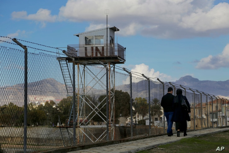A couple walks past a U.N. guard post at the fence that divides the Greek and Turkish Cypriots areas, as they stroll at the Turkish Cypriot northern part of the divided capital Nicosia in the eastern Mediterranean island of Cyprus, Jan. 11, 2017.