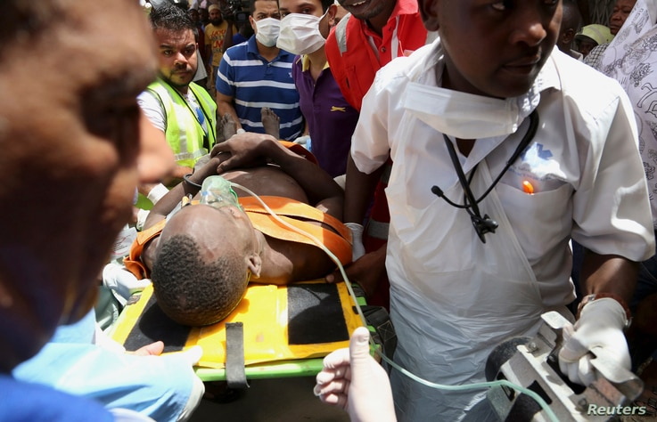 Paramedics assist a construction worker who was rescued from a collapsed building in the Kariakoo district of central Dar es Salaam, Tanzania, March 29, 2013.