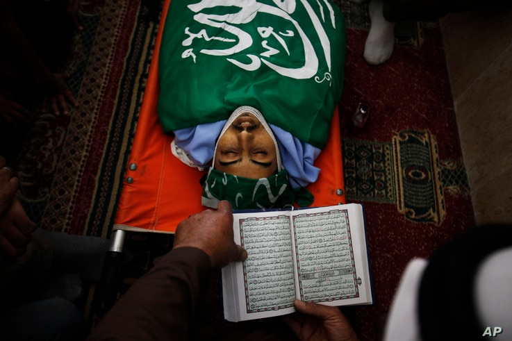 A Palestinian reads from the Quran during the funeral of Munir Badarin, who was shot during clashes with Israeli soldiers in the West Bank village of Samoa, south of Hebron, July 14, 2014.