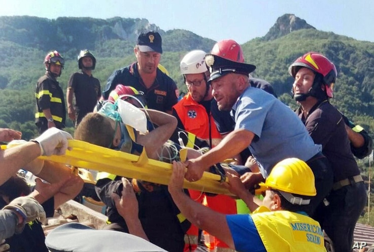 Firefighters and rescuers pull out a boy, Mattias, from the collapsed building in Casamicciola, on the island of Ischia, near Naples, Italy, a day after a 4.0-magnitude quake hit the Italian resort island, Aug. 22, 2017.