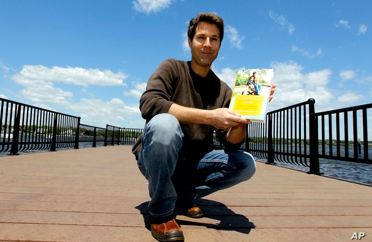 """FILE - David Goldman poses with his book """"A Father's Love"""" in Red Bank, N.J., May 5, 2011. Goldman became the poster dad for the issue of international child abductions when his ex-wife ran off with his son, Sean, to Brazil. He finally got custody of..."""