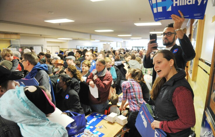 Hillary Clinton volunteers work the crowd for their candidate at the Democratic party caucus in Anchorage, Alaska, March 26, 2016.