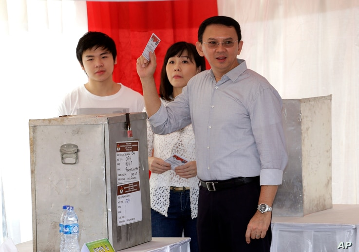 """Jakarta Governor Basuki """"Ahok"""" Tjahaja Purnama who is seeking for his second term in office, his wife Veronica and son Nicholas, left, cast their ballot at a polling station during the runoff election in Jakarta, Indonesia, April 19, 2017."""