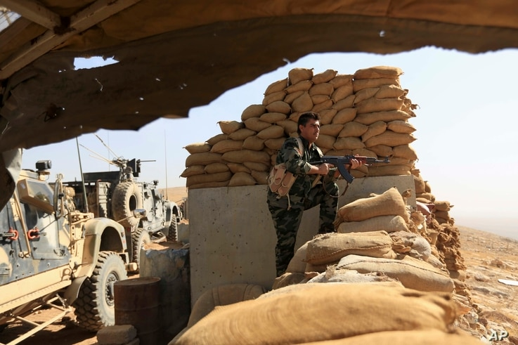 An Iraqi Kurdish peshmerga fighter stands guard outside Bartella, Iraq, Oct. 21, 2016. The historically Christian town is located some 15 kilometers (9 miles) from Mosul's outskirts.