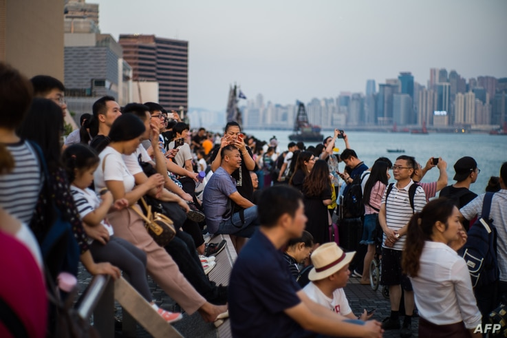 "Tourists visit a Kowloon promenade along Victoria Harbor in Hong Kong, Oct. 3, 2018, during China's ""Golden Week"" holiday that runs from Oct. 1 to 7."