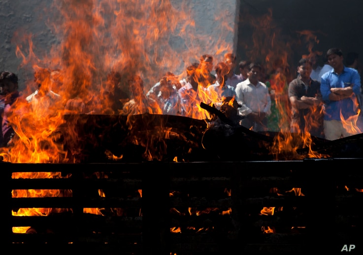 Flames rise from the cremation pyre of Srinivas Kuchibhotla, a 32-year-old engineer who was killed in an apparently racially motivated shooting in a crowded Kansas bar, at a crematorium in Hyderabad, India, Tuesday, Feb.28, 2017.