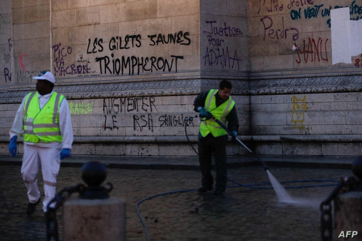 "Workers clean around the Arc de Triomphe a day after a yellow vests (gilets jaunes) demonstration against rising oil prices and living costs, Dec. 2, 2018 in Paris. Graffiti on the monument reads ""yellow vests will triumph."""