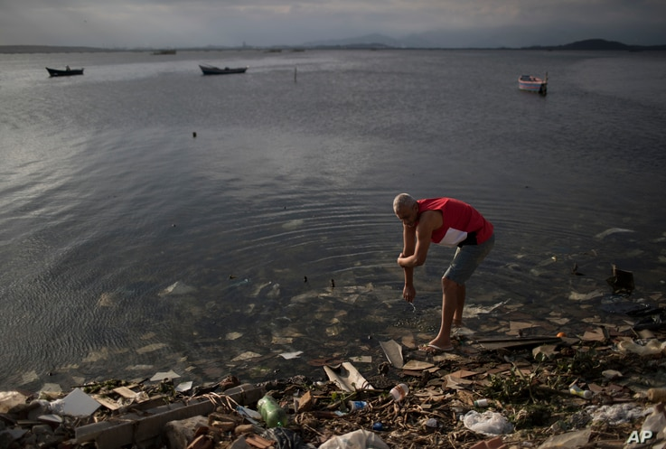 A man washes himself in the polluted waters of Guanabara Bay in Rio de Janeiro, Brazil, July 30, 2016.