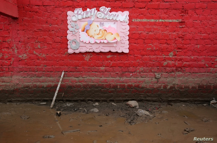 A baby shower sign hands on a wall at the home of Carlos Rojas after rivers breached their banks due to torrential rains, causing flooding and widespread destruction in Carapongo Huachipa, Lima, Peru, March 21, 2017.