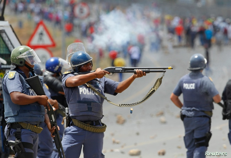 FILE - Police fire on demonstrators during a strike by farm workers at De Doorns on the N1 highway, linking Cape Town and Johannesburg, Jan. 9, 2013.