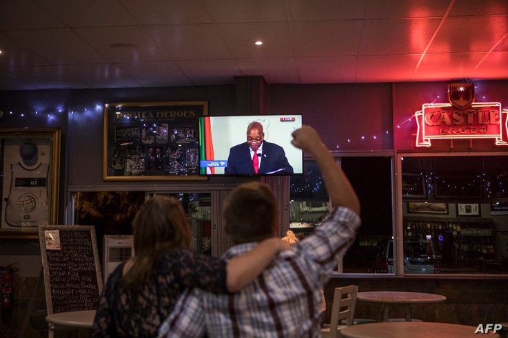 A customer reacts while watching a telecast in a bar in Randburg, Johannesburg, on Feb. 14, 2018, as South African president Jacob Zuma makes a live address to the nation.
