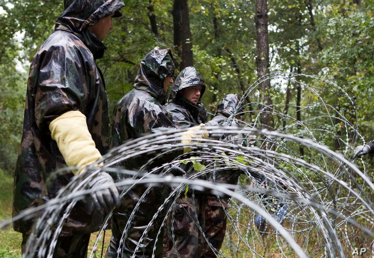 Hungarian soldiers put up spools of razor wire on Slovenian border in Zitkovci, Sept. 25, 2015. Hungary has installed spools of razor wire near a border crossing with Slovenia, which like Hungary is part of the EU's Schengen zone of passport-free tra