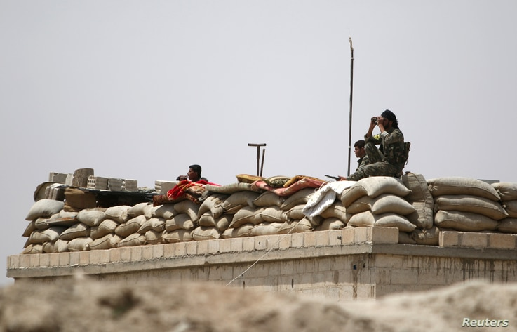 Fighters of the Syria Democratic Forces held a watchful position near Raqqa, Syria, May 27, 2016. U.S. officials believe the SDF  is ready to at least start encircling the Islamic State stronghold, while planning for its liberation.