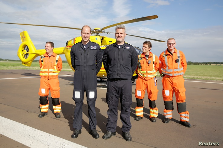 Britain's Prince William poses with crew members of the East Anglian Air Ambulance at Cambridge Airport, England, July 27, 2017.