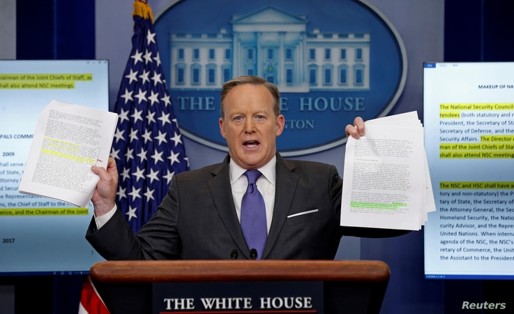 White House spokesman Sean Spicer holds up documents comparing the makeup of the National Security Council (NSC) in the Trump and Obama administrations during his press briefing at the White House in Washington, D.C., Jan. 30, 2017.