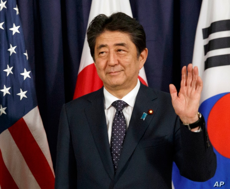 FILE - Japanese Prime Minister Shinzo Abe gestures as he meets with U.S. President Donald Trump and South Korean President Moon Jae-in before the Northeast Asia Security dinner in Hamburg, July 6, 2017. His poll numbers have bounced back to around 50...