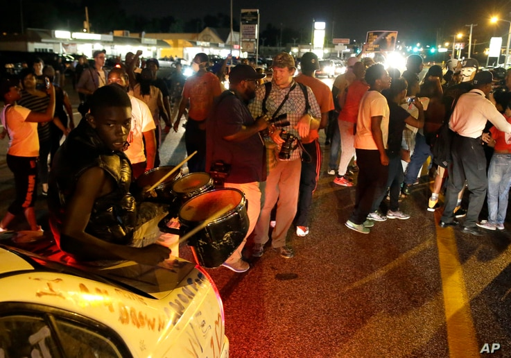 Protesters gather along West Florissant Avenue during a demonstration in Ferguson, Mo., Tuesday, Aug. 11, 2015. The St. Louis suburb has seen demonstrations for days marking the anniversary of the death of 18-year-old Michael Brown, whose shooting de...