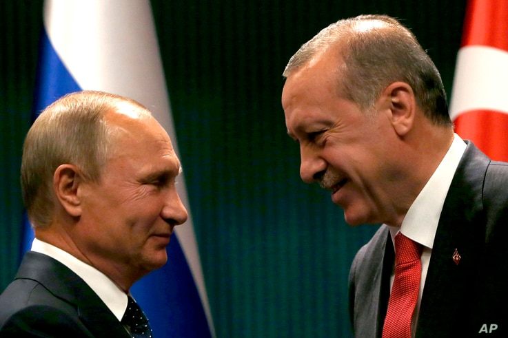 FILE - In this Sept. 28, 2017 file photo, Turkish President Recep Tayyip Erdogan, right, shakes hands with Russian President Vladimir Putin in Ankara, Turkey.