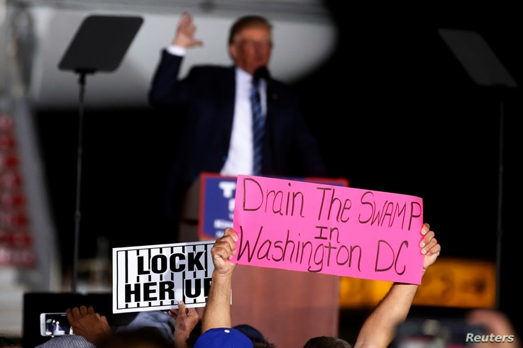 """A man holds up a """"Drain the Swamp in Washington DC"""" sign as then-Republican presidential nominee Donald Trump attends a campaign event on the tarmac of the airport in Kinston, North Carolina, Oct. 26 2016."""