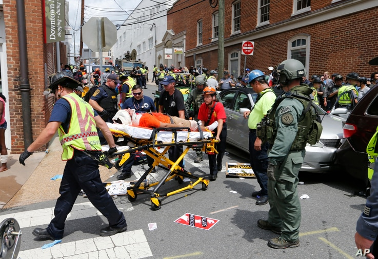 Rescue personnel help injured people after a car ran into a large group of protesters after an white nationalist rally in Charlottesville, Va., Aug. 12, 2017.