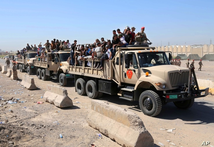 Iraqi men fill military trucks to join the Iraqi army at the main recruiting center in Baghdad, June 17, 2014.