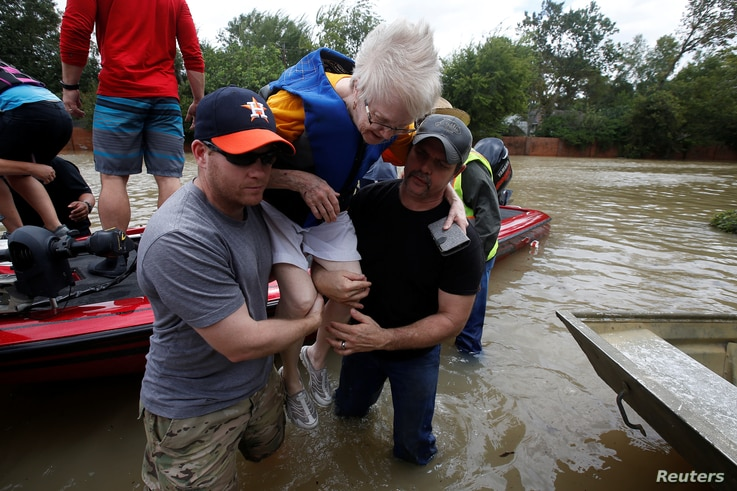 Volunteers help a woman from a rescue boat as it evacuates people from the rising waters of Buffalo Bayou following Hurricane Harvey in a neighborhood west of Houston, Texas, Aug. 30, 2017.