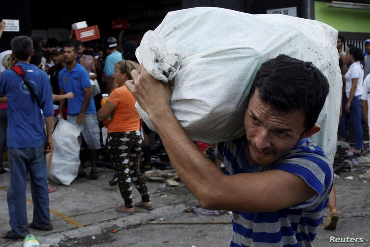 People carry goods taken from a food store in La Fria, Venezuela, Dec. 17, 2016.