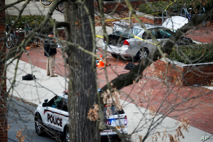 A car sits inside a police line as authorities respond to an attack at Ohio State University, Nov. 28, 2016, in Columbus, Ohio. A man plowed his car into a group of pedestrians and began stabbing people before he was shot to death by a police officer...
