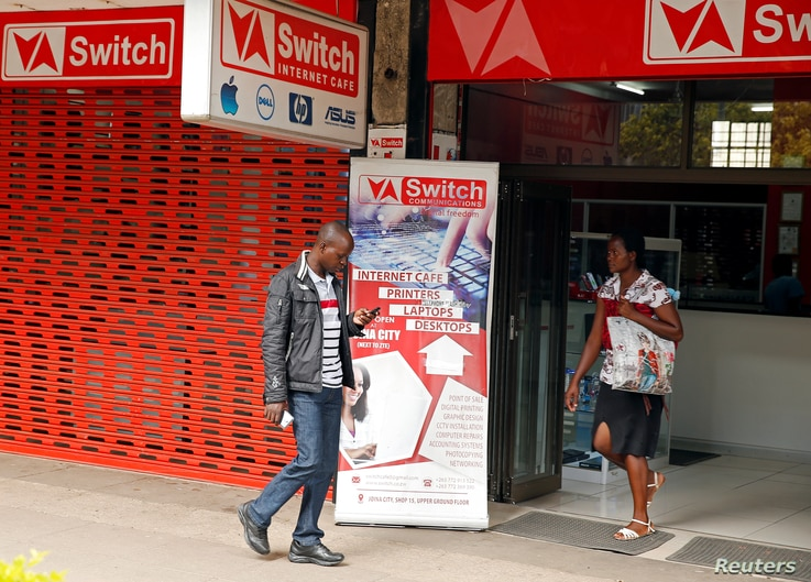 FILE - A man checks his mobile phone outside an internet cafe in Harare, Zimbabwe, Jan. 21, 2019.