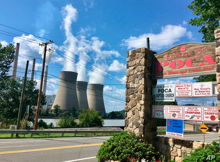 In this Aug. 23, 2018 photo, American Electric Power's John Amos coal-fired plant in Winfield, West Virginia, is seen from the town of Poca across the Kanawha River.
