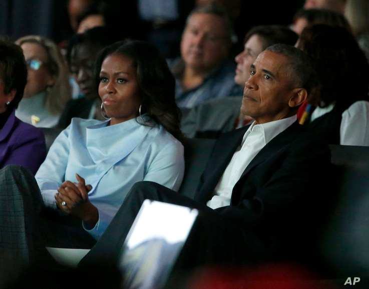 Former President Barack Obama, right, and former first lady Michelle Obama listen to a speaker at the first session of the Obama Foundation Summit in Chicago, Oct. 31, 2017.