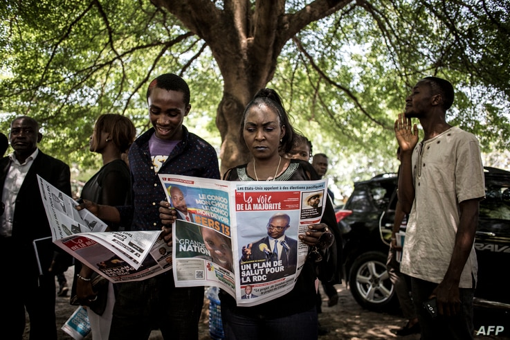 Supporters of the official DRCongo Presidential candidate, Emmanuel Ramazani Shadary, read a newspaper outside the Cathedral Notre-Dame Du Congo in Kinshasa, Nov. 24, 2018, during the launch of his official electoral campaign.