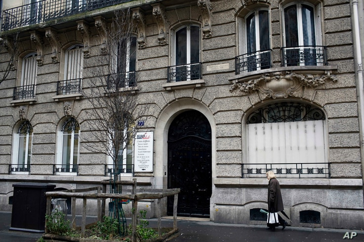 A woman walks past a building on Avenue Parmentier in Paris on Friday, Jan. 25, 2019. The address was supposedly the home of CPW-Consulting.