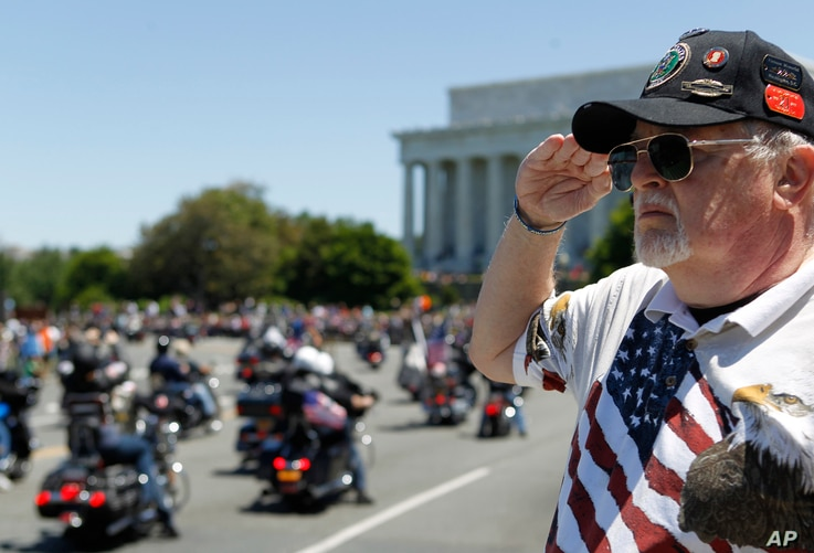 "Ken Caryl of Dale City, Virginia salutes the motorcyclists, many of them are veterans, as they ride across the Memorial Bridge into Washington during the annual Rolling Thunder ""Ride for Freedom,"" May 26, 2013."