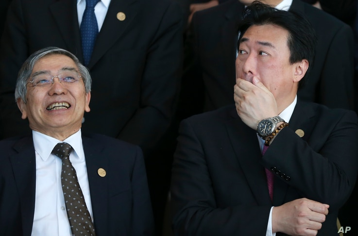 Haruhiko Kuroda, governor of the Bank of Japan, left, and Japan's Vice Finance Minister Minoru Kihara talk before posing for a group picture at the G-20 finance ministers and central bankers summit in Buenos Aires, Argentina, March 19, 2018.