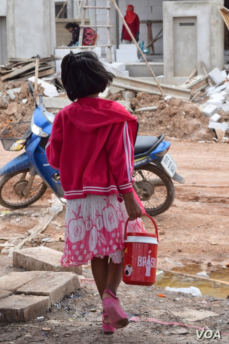 A girl goes on an errand at a construction site, angkok, July 10, 2014. (Steve Herman/VOA)