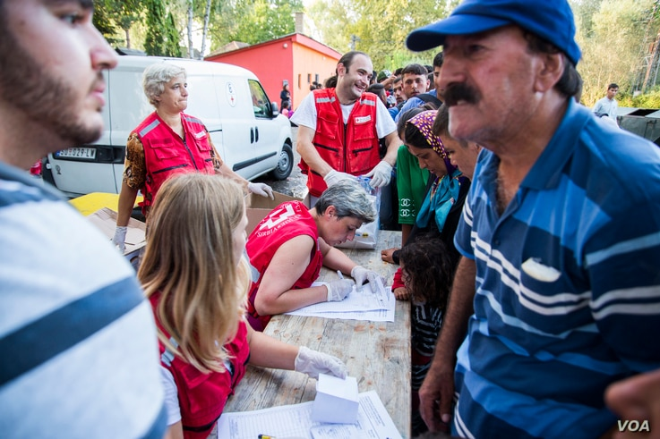 Serbian Red Cross giving food and water to migrants. (A. Tanzeem/VOA)