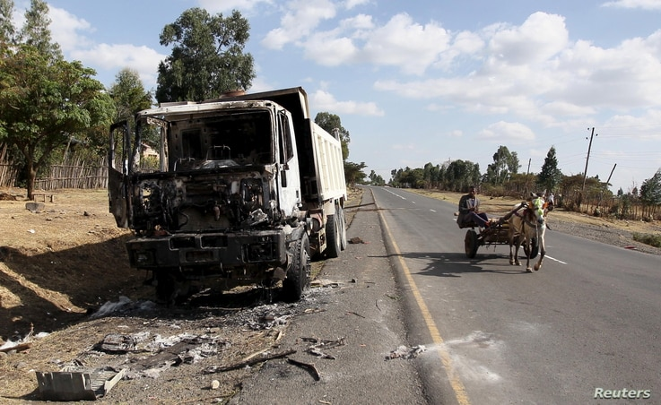 A man drives a horse-cart past the wreckage of a truck torched during recent demonstrations along the road in Holonkomi town, in Oromia region of Ethiopia, Dec. 17, 2015.