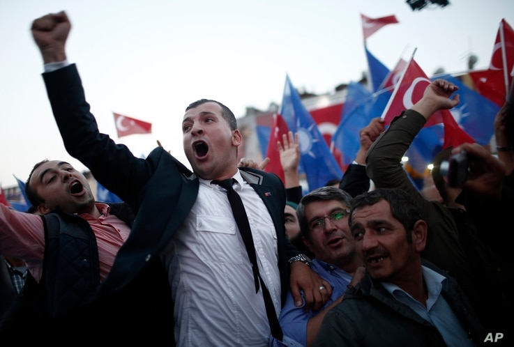 Supporters of Turkey's Justice and Development Party (AKP) celebrate as their leader and Turkish Prime Minister Ahmet Davutoglu arrives to deliver a speech during a rally,  in Istanbul, Turkey, Oct. 7, 2015.