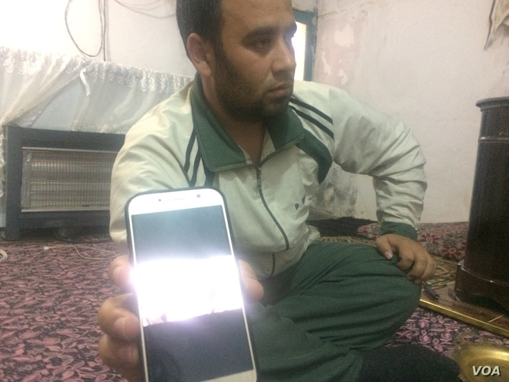 Hussien and family fled Syria in 2013 after 16 of their neighbors were killed in a bomb strike.  He shows a picture on his mobile phone of his injured father in Turkey five years later after a rocket strike. Pictured on Feb. 3, 2018 in a village near...