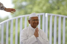 Veteran Indian social activist Anna Hazare clasps his hands together as he greets supporters after arriving for his hunger strike at Rajghat in New Delhi, June 8, 2011