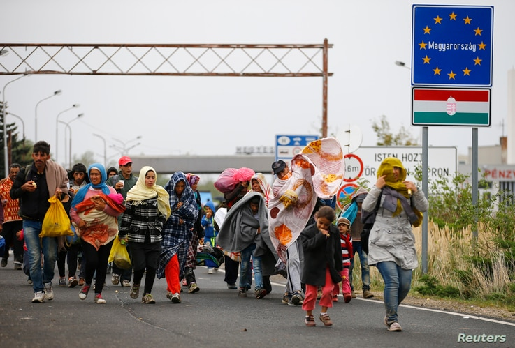 Migrants walk as they cross the border from Hungary to Nickelsdorf, Austria, September 25, 2015. The United Nations said on Friday it could see no easing of the flow of refugees into Europe, with 8,000 arrivals daily, and that problems now facing gov...