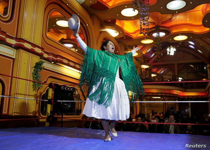 A Cholita (Andean woman) fighter greets before their wrestling session at the Havana Hotel Cholet in El Alto, outskirts in La Paz, Bolivia, June 29, 2018.