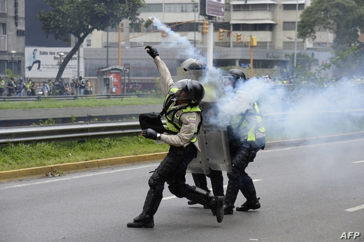 Policemen clash with demonstrators protesting against new emergency powers decreed this week by President Nicolas Maduro in Caracas on May 18, 2016.