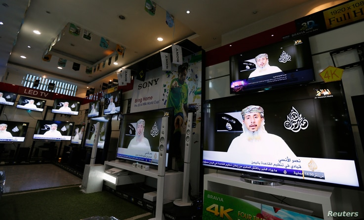 Nasr al-Ansi, a leader of the Yemeni branch of al-Qaida (AQAP), is shown on televisions at a shop, delivering a message in which AQAP claims responsibility for the attack on Charlie Hebdo last week, in Sanaa, Yemen, Jan. 14, 2015.