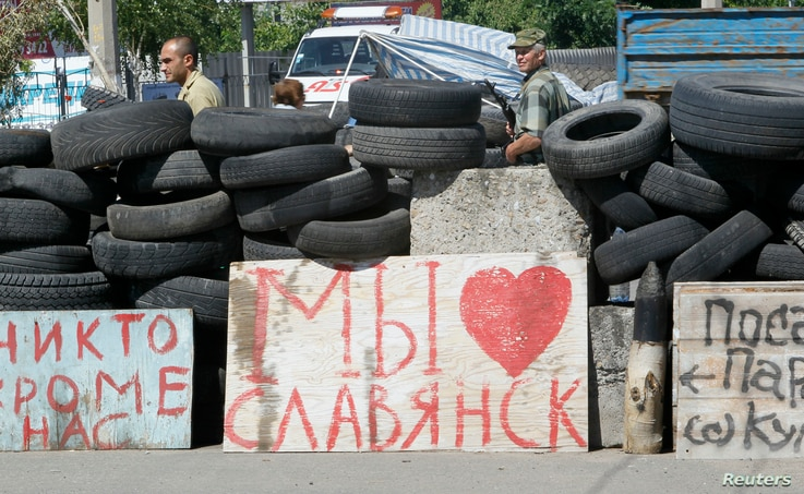"""Pro-Russian separatists stand guard at a checkpoint, where a sigh reads """"We love Slovyansk,"""" in the eastern city of Slovyansk, Ukraine, July 1, 2014."""