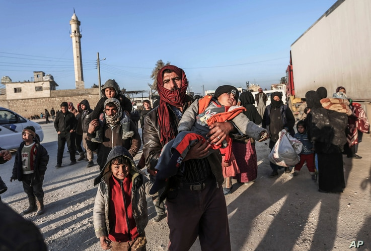 Syrians gather at the Bab al-Salam border gate with Turkey, in Syria, Feb. 6, 2016.
