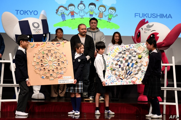 Elementary school students from Fukushima (L) and Tokyo (R) exchange mementos during an event marking 500 days till the Tokyo 2020 Olympic Games in Tokyo, March 12, 2019.